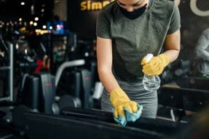 Young female worker disinfecting and cleaning gym equipment