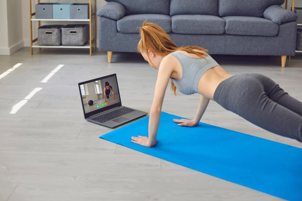 Sport home online.Young woman exercising during online training | Fitness Expo