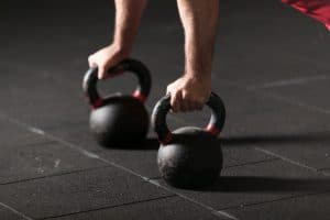 man lifting kettle bells - Fitness Expo